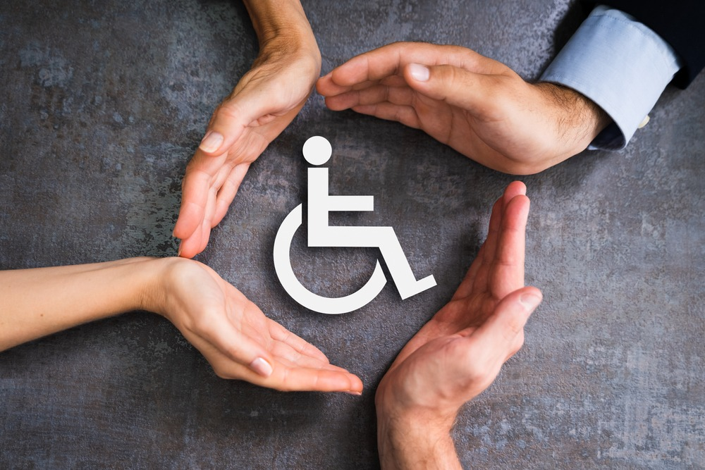 hands forming a circle around a disability symbol